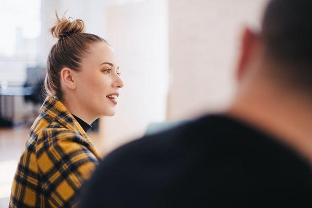 nuori nainen istuu ja puhuu kuvattuna sivusta