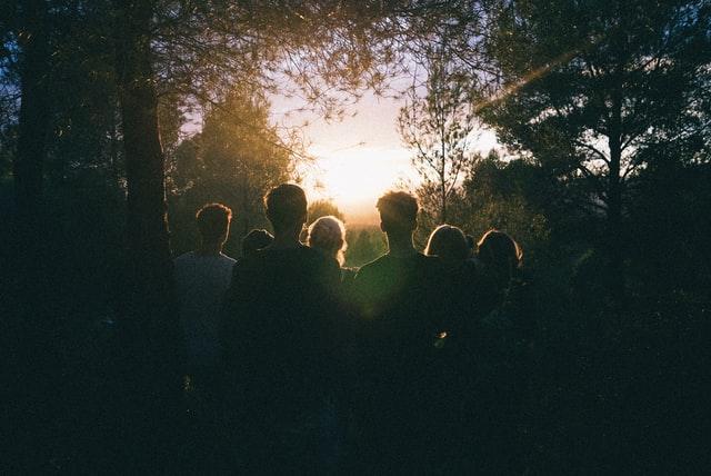 ihmisjoukko selin metsässä kääntyneenä valoa kohti