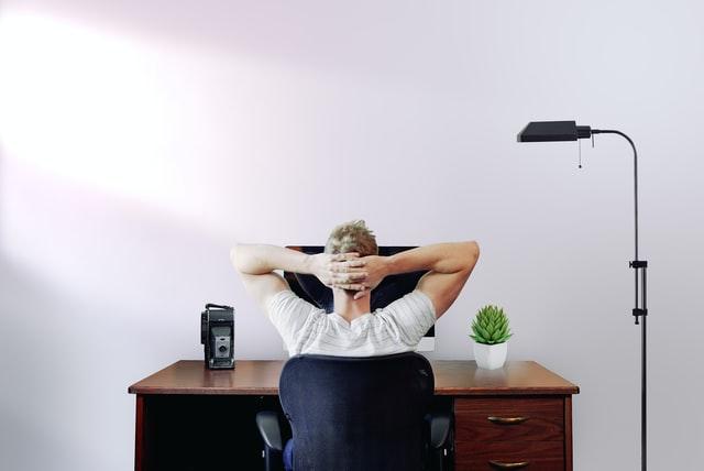 Valkopaitainen mies istuu tietokoneen ääressä ja on ristinyt kädet takaraivolle. Mies nojaa tuolin selkänojaan.